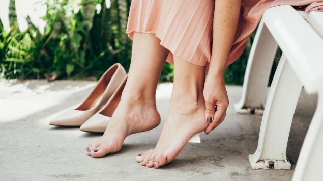 Eine Frau hat ihre Schuhe ausgezogen und berührt ihre Ferse.