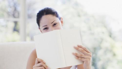 Eine junge lächelnde Frau hält ein Buch vors Gesicht, sodass ihr Mund verdeckt ist.