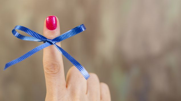 Jemand hat eine blaue Schleife um den Finger gebunden.