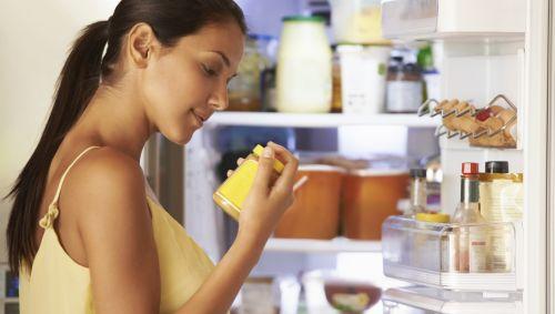 Eine Frau steht vor dem geöffneten Kühlschrank und schaut sich ein Lebensmittel an.