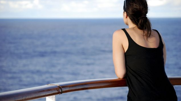 Eine Frau lehnt an der Reling und blickt aufs Meer.