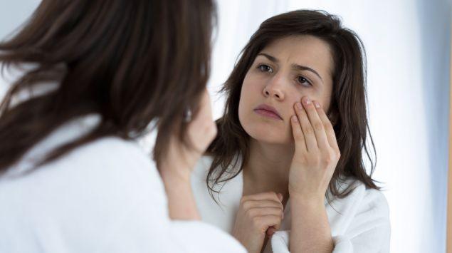 Eine Frau betrachtet ihr Gesicht kritisch im Spiegel und fasst sich mit einer Hand ins Gesicht.