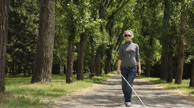 Eine blinde Frau läuft auf einem Parkweg.