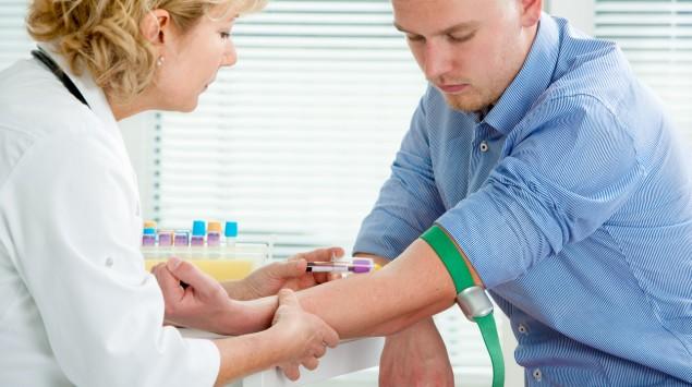 Eine Frau in weißem Kittel nimmt einem Mann am linlen Arm Blut ab.