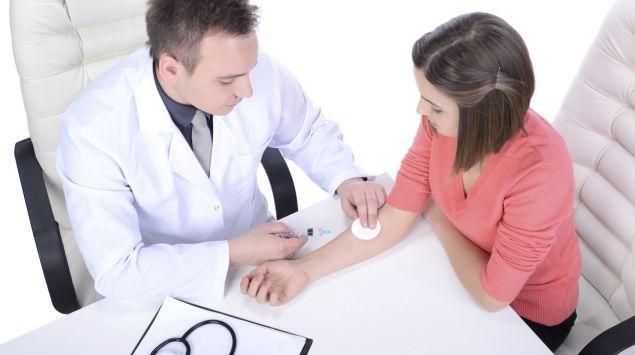 Ein Arzt nimmt bei einer Patientin Blut ab.