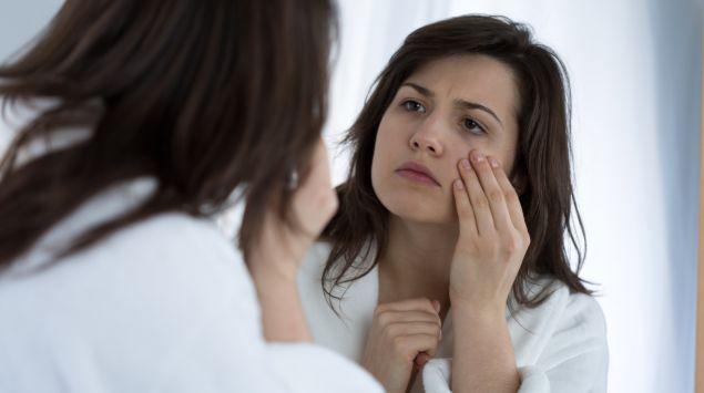 Eine blasse Frau schaut in den Spiegel.