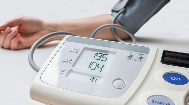Man  sieht ein digitales Blutdruckmessgerät und einen Arm mit Oberarm-Manschette.