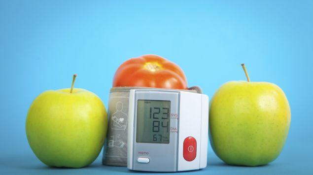 Man sieht zwei Äpfel und eine Tomate neben einem Blutdruckmessgerät.