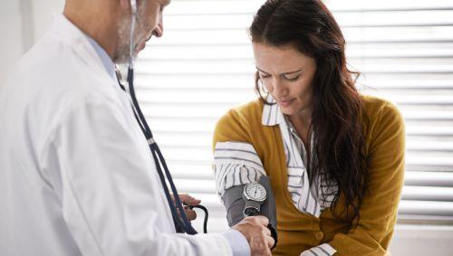 Ein Arzt in weißem Kittel misst bei einer Frau den Blutdruck.
