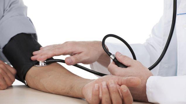 Ein Arzt misst bei einem Mann den Blutdruck.
