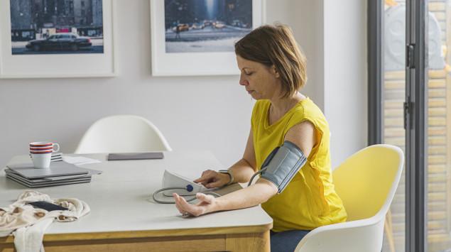 Eine Frau misst ihren Blutdruck am Oberarm.