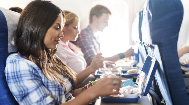 Zwei junge Frauen und ein junger Mann, die im Flugzeug nebeneinander sitzen, nehmen eine Bordmahlzeit zu sich.