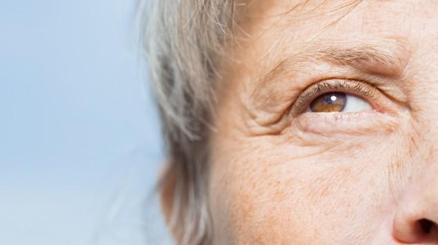 Zu sehen ist ein braunes Auge einer grauhaarigen Person in Nahaufnahme vor blauem Himmel.