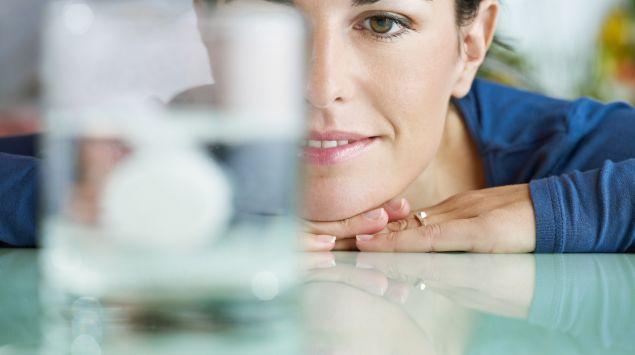 Eine Frau schaut zu, wie sich eine Brausetablette in Wasser auflöst.
