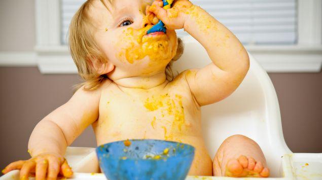 Ein Baby matscht mit dem Brei.