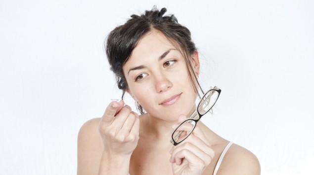 Eine Frau hält eine Brille in der linken Hand und betrachtet eine auf ihrem rechten Zeigefinger liegende Kontaktlinse.