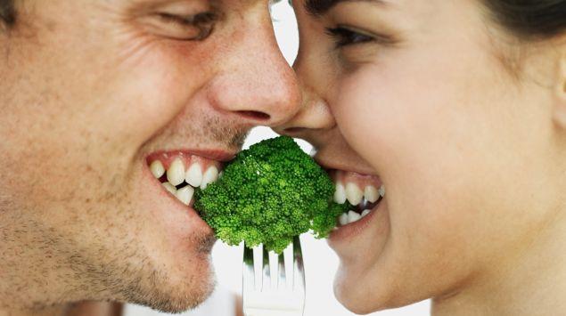Das Bild zeigt ein Pärchen, das in etwas Brokkoli beißt.