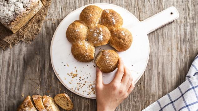 Eine Hand greift nach einem von drei verschiedenen Brotsorten auf einem Holztisch.