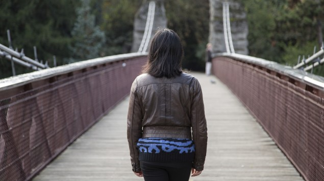 Eine Frau geht über eine Brücke.