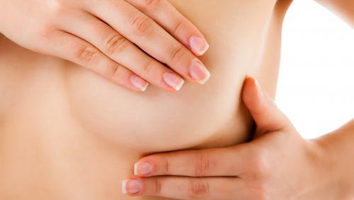 Eine Frau tastet ihre Brust ab.