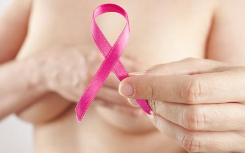 Eine Frau verdeckt ihre Brüste und hält eine pinke Brustkrebsschleife in der Hand.