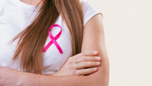 Eine Frau trägt eine rosa Schleife auf dem Shirt.
