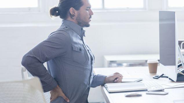 Das Bild zeigt einen Mann, der vor einem Bildschirm sitzt und seinen Rücken hält.
