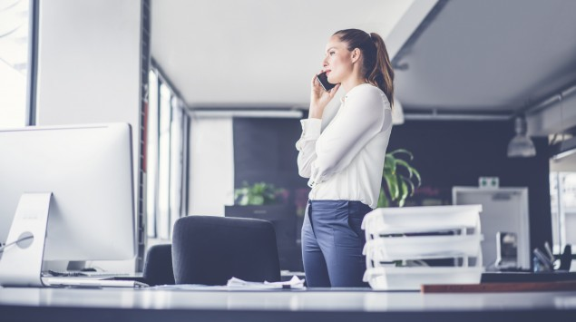 Frau steht im Büro und telefoniert