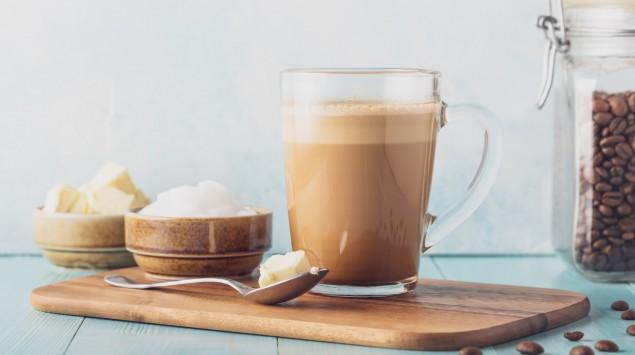 Auf einem Tisch stehen ein Henkelglas mit Buletproof-Coffee neben einem Glas Kaffee-Bohnen und einem Schälchen mit Butter.