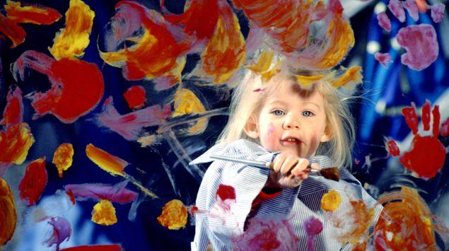 Mädchen malt eine Glasscheibe bunt an
