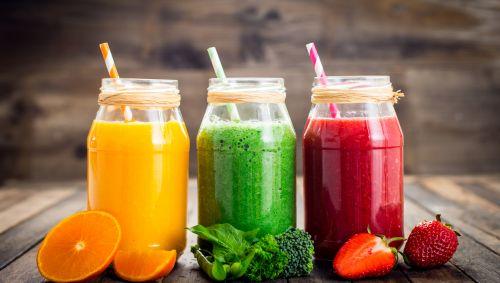 Auf einem Tisch stehen drei Gläser, gefüllt mit einem gelben, einem grünen und einem roten Smoothie.