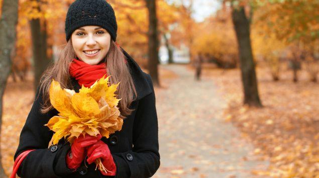 Eine junge Frau in einem herbstlichen Park, sie hält einen Strauß orangener Herbstblätter in der Hand.