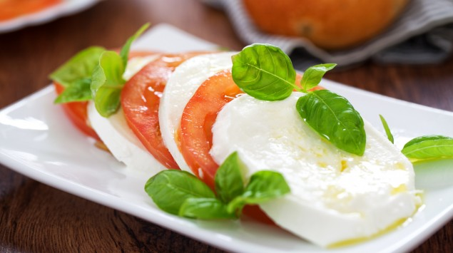 Auf einem Tisch steht ein kleiner Teller mit Caprese-Salat.