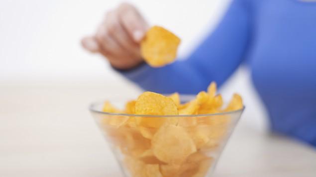 Eine Frau greift in eine Schüssel mit Chips.