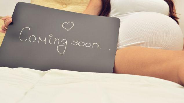 """Eine Schwangere mit Schild """"coming soon""""."""
