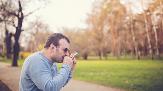 Das Bild zeigt einen jungen Mann, der hustet und eine Zigarette in der Hand hält.