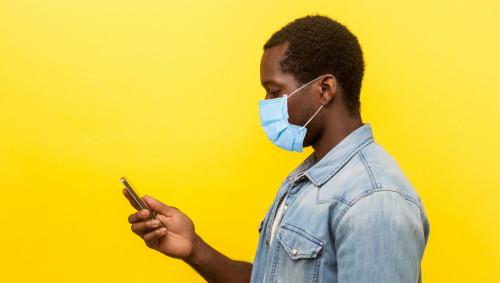 Ein Mann mit Maske schaut auf sein Smartphone
