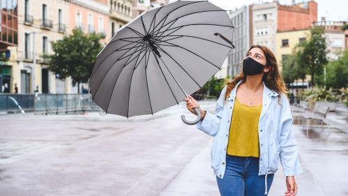 Eine Frau mit Mundschutz hält den Schirm zur Seite und schaut in den Himmel