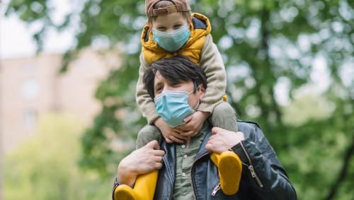 Ein Vater hat seinen Sohn auf den Schultern, beide tragen eine Maske.
