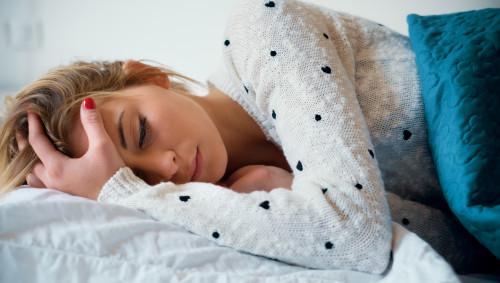 Ein Mädchen liegt im Bett und hält sich den Kopf