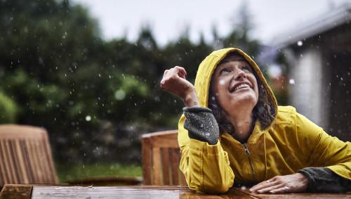 Eine Frau mit Regenjacke sitzt im Schneeregen und lacht