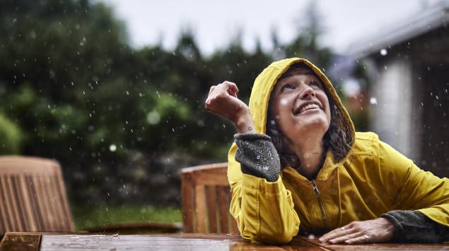 eine Frau mit Regenjacke sitzt im Regen und lacht: Nach überstandener Infektion ist man immun gegen das Coronavirus