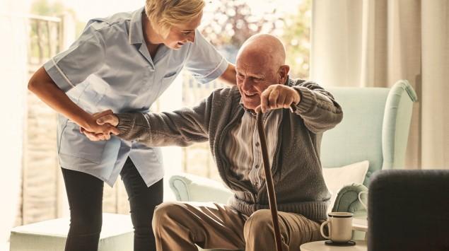 Eine Pflegerin hilft einem älteren Mann dabei, aus dem Sessel aufzustehen.