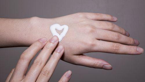 Das Bild zeigt ein Herz aus Creme auf einer Hand-