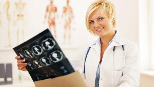Eine Ärztin hält ein Schädel-CT in der Hand.