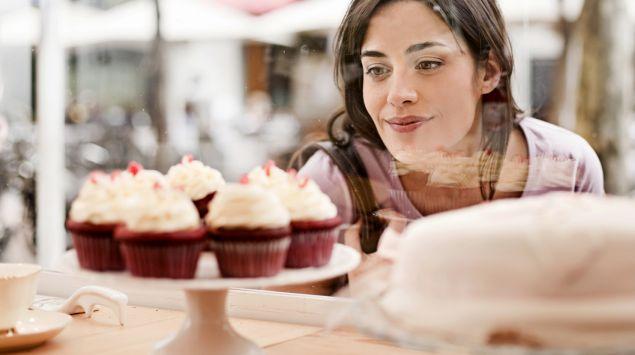 Eine junge Frau betrachtet Cupcakes im Schaufenster.