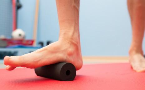 Fersenschmerzen: Jemand rollt seinen Fuß über eine kleine Faszienrolle.