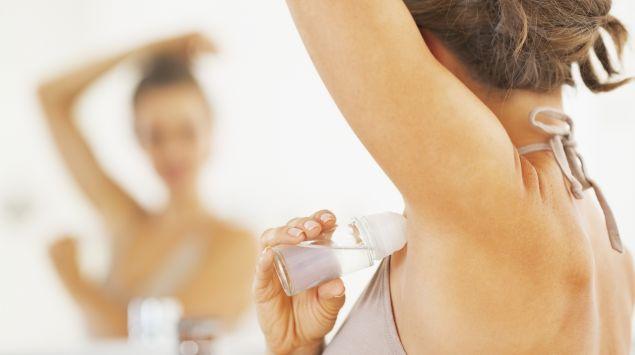 Einen Frau benutzt vorm Spiegel einen Deoroller.