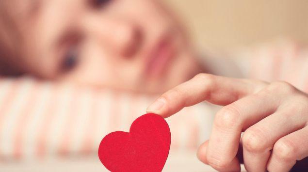 Eine traurig aussehende Frau hält ein rotes Herz in der Hand.