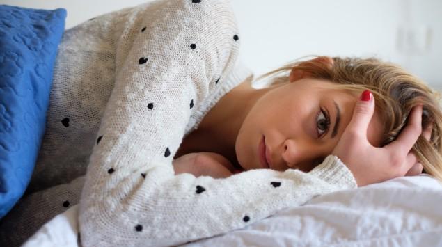 Junge Frau liegt unglücklich im Bett.
